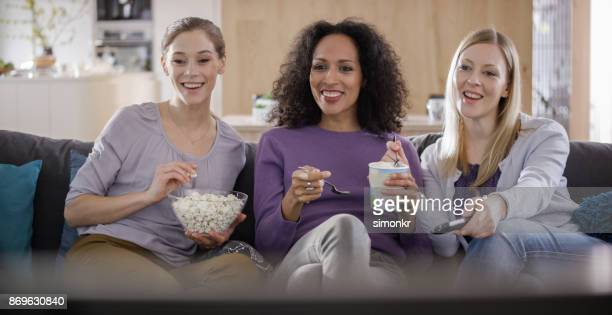 Three female friends talking while watching TV and eating popcorn