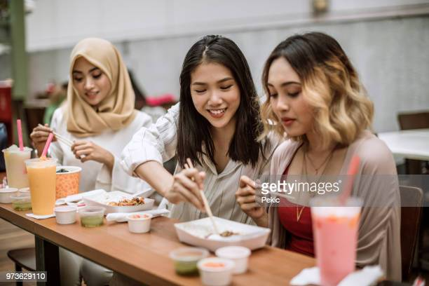 three female friends tasting exotic asian cuisine - malaysian culture stock pictures, royalty-free photos & images