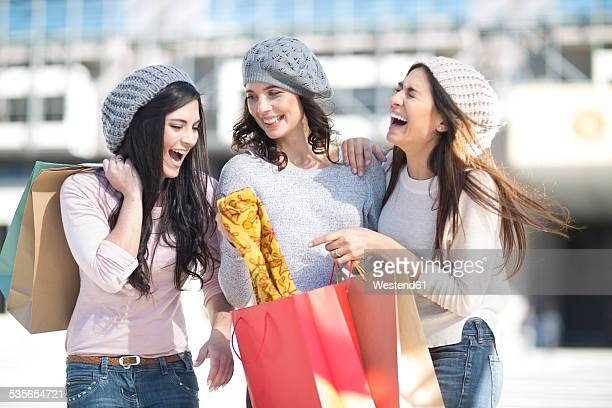 Three female friends with wool caps and shopping bags