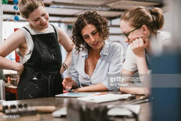 three female jewellers looking at digital tablet at workbench meeting - customised stock pictures, royalty-free photos & images