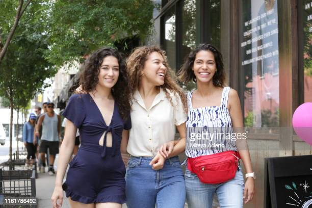 three female latinx millennials enjoy a walk down a new york city street. - waist pack stock pictures, royalty-free photos & images