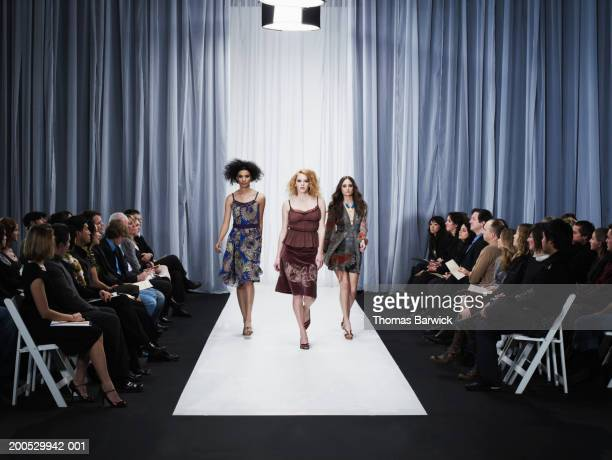three female models walking down runway - fashion runway stock pictures, royalty-free photos & images
