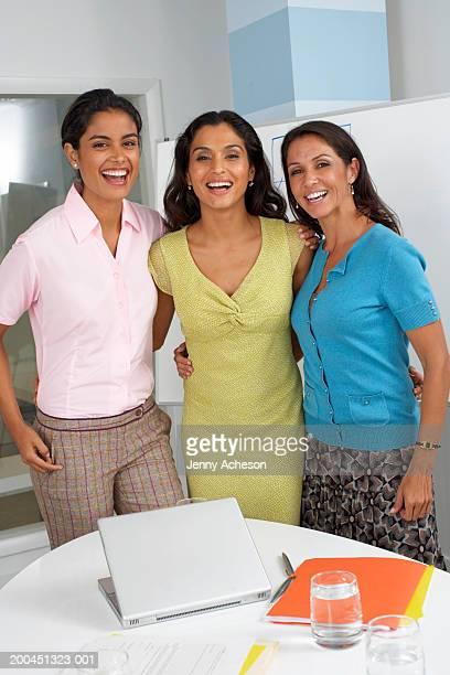 Three female office workers in standing in meeting room, portrait