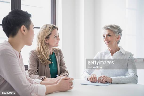 Three female professional colleagues in business meeting