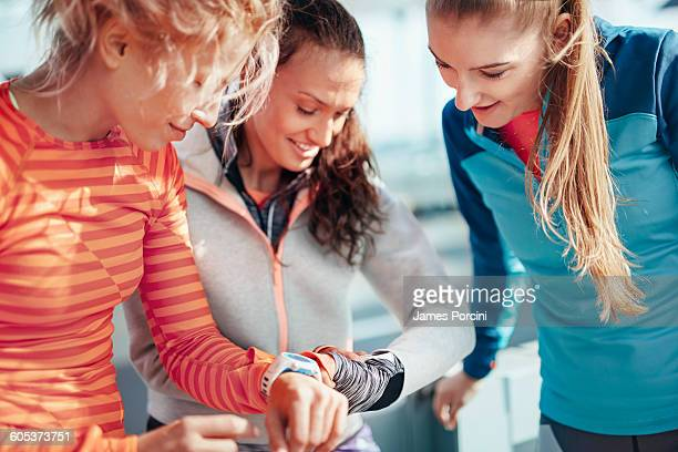 Three female runners checking time on smartwatches