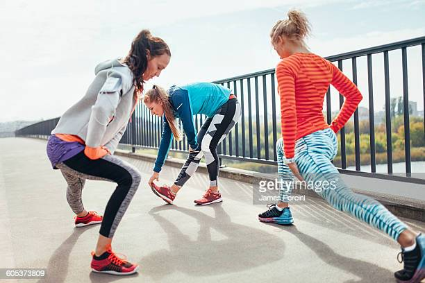 Three female runners doing warm up exercise on footbridge