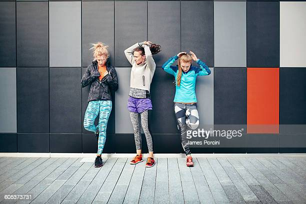 Three female runners putting up their hair in city underpass