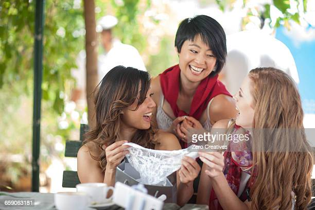 Three female shopping friends laughing at new knickers at sidewalk cafe in city