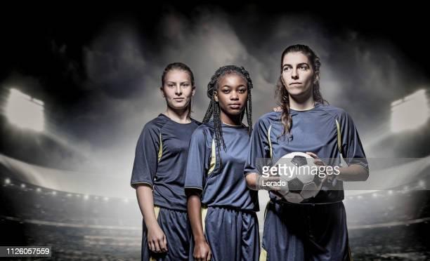 drei weibliche fußball-spieler - frauenfußball stock-fotos und bilder