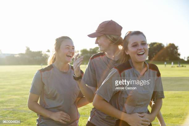 three female sports players embrace and show their friendship on the sports field - women cricket stock pictures, royalty-free photos & images