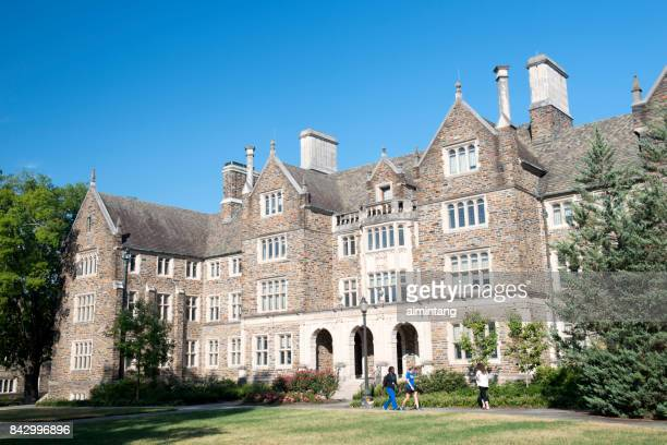 three female students walking past a dorm building in the campus of duke university - duke stock pictures, royalty-free photos & images