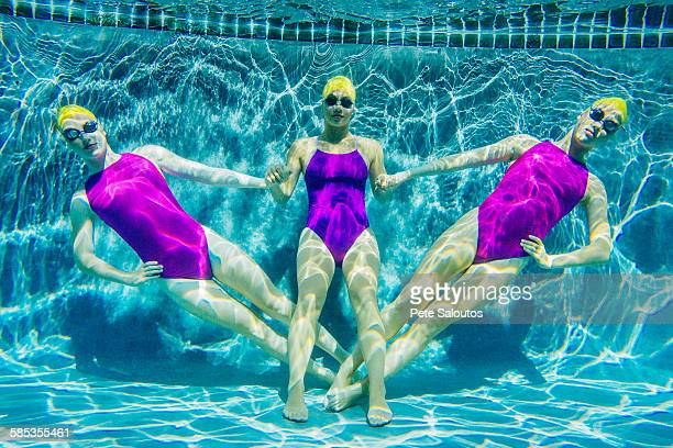 Three female swimmers, underwater, holding hands