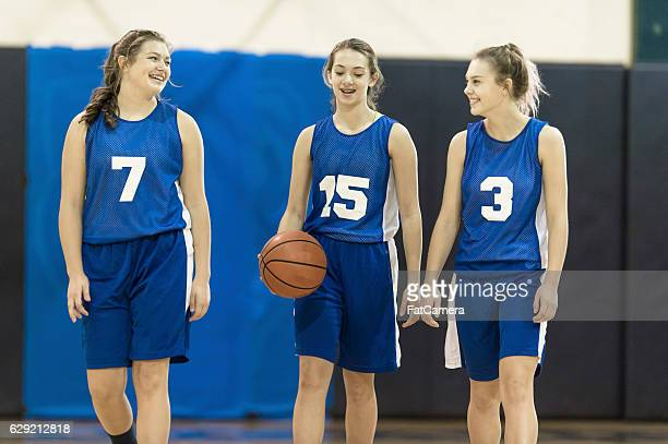 Three female teenage basketball players walking together