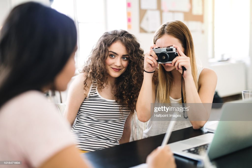 Three female teenager friends with digital camera indoors, taking photo of each other. : Stock Photo