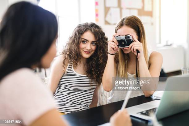 Three female teenager friends with digital camera indoors, taking photo of each other.