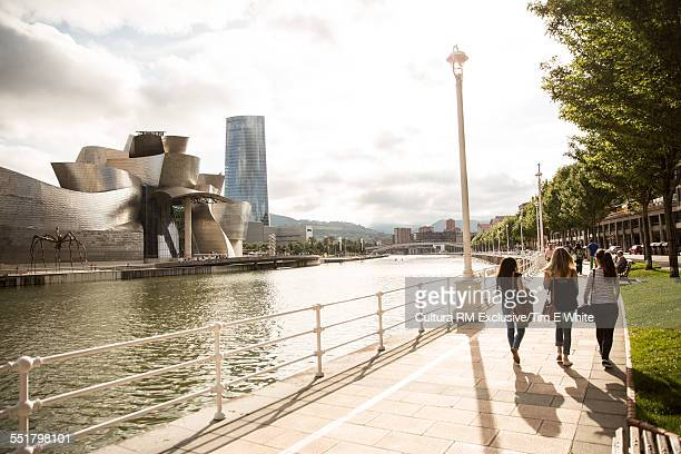 Three female tourists strolling on waterfront, Guggenheim museum, Bilbao, Spain