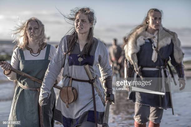 three female vikings posing in front of a group of warriors stood in the surf on the shore - medieval stock pictures, royalty-free photos & images