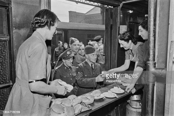 Three female workers from the Young Men's Christian Association serve tea and rolls to British servicemen from their canteen in a train carriage at a...