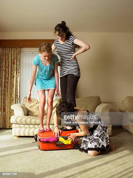 Three females trying to close suitcase.
