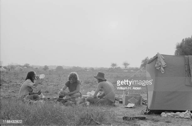 Three festival-goers relaxing at the campsite of Reading Festival a day before the official start, Richfield Avenue, Reading, UK, 26th August 1976.