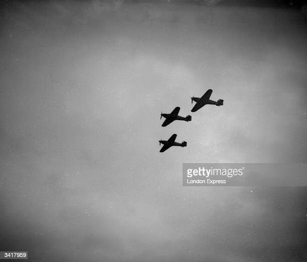 Three fighter planes flying in formation.
