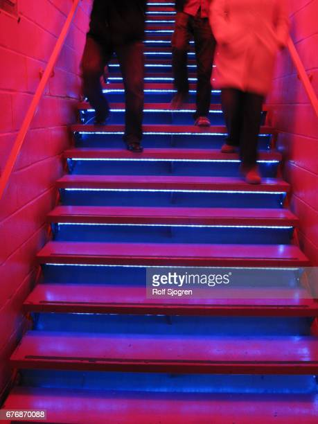 Three figures descending neon-lit staircase