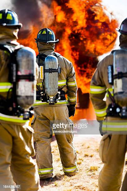 three firefighters watching blazing fire - extinguishing stock pictures, royalty-free photos & images