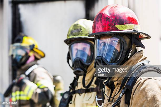 Three firefighters wearing oxygen masks