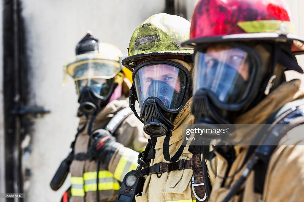 Three firefighters wearing oxygen masks : Stock Photo