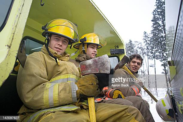 three firefighters with axes sitting in the back of a fire truck