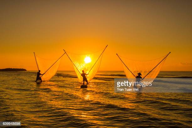 three fisherman with golden fishing net, sun, dawn, vietnam - ナムディン ストックフォトと画像