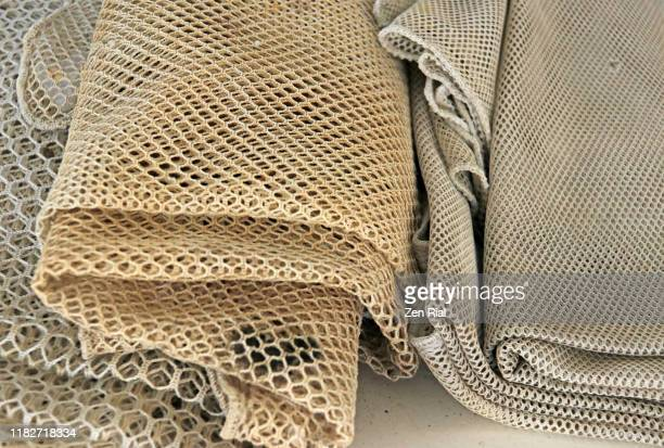three fishing nets with different hole sizes folded on display in an aquatic center - malla textil fotografías e imágenes de stock