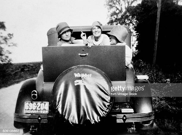 Three flappers pose in the jump seat of a Whippet car ca 1928