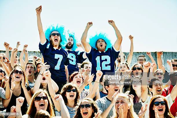 Three football fans leading crowd in cheer