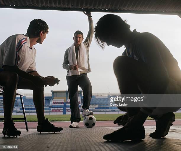 Three footballers in stadium tunnel