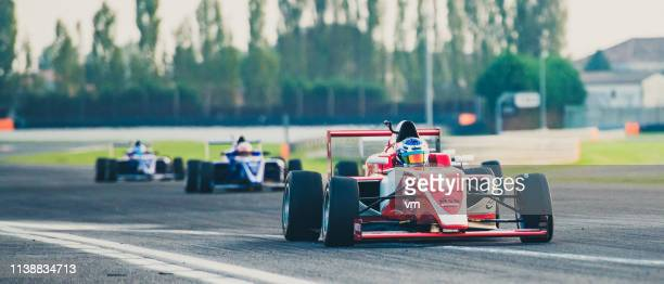 three formula race cars on the race track - grand prix motor racing stock pictures, royalty-free photos & images