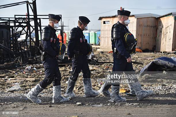 TOPSHOT Three French policemen wearing boots protected with plastic walk in the 'Jungle' migrant camp in Calais northern France on October 27 during...