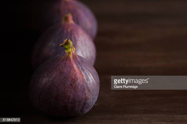 three fresh figs on a wooden surface - claire plumridge stock pictures, royalty-free photos & images