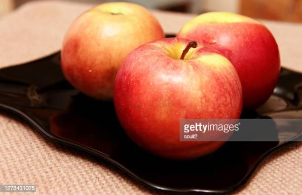 three fresh red apples black plate