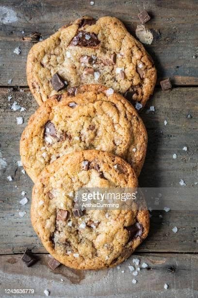 木製の背景に焼きたてのチョコチップクッキー3個 - チョコレートチップクッキー ストックフォトと画像