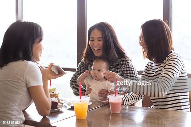 three friends and a baby in a cafe together - japanese mom stock photos and pictures