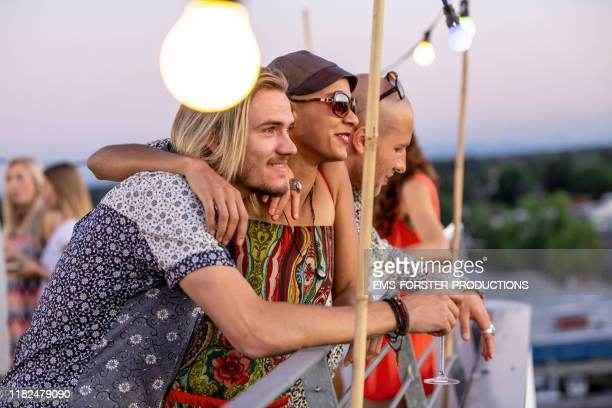 three friends are enjoying a summer party on a urban rooftop in munich and looking into an amazing sunset - munich stock pictures, royalty-free photos & images
