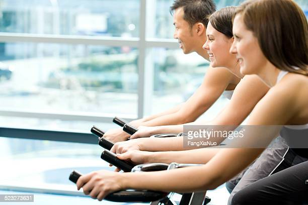 Three Friends Are In A Spinning Class At A Gym
