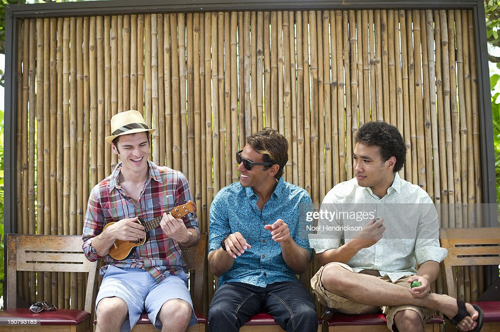Three friends at a cafe playing instruments : Stock-Foto