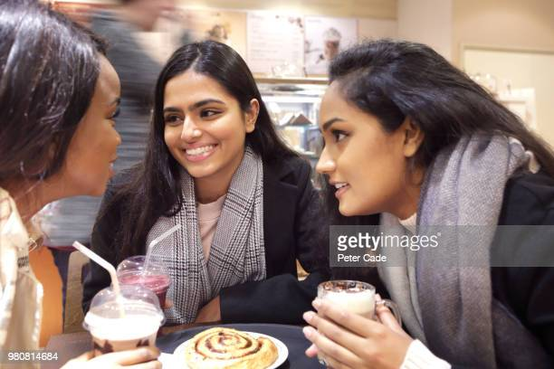 Three friends at table talking in coffee shop