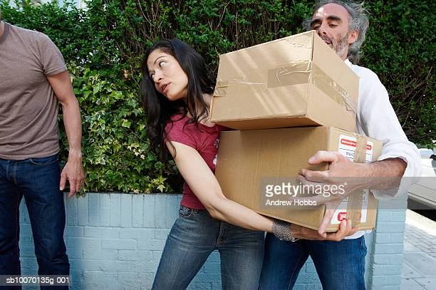 Drei Freunde tragen Karton Kartons außerhalb Haus