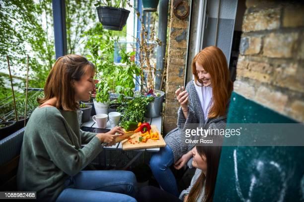 three friends cutting vegetables on the balcony - balkon stockfoto's en -beelden