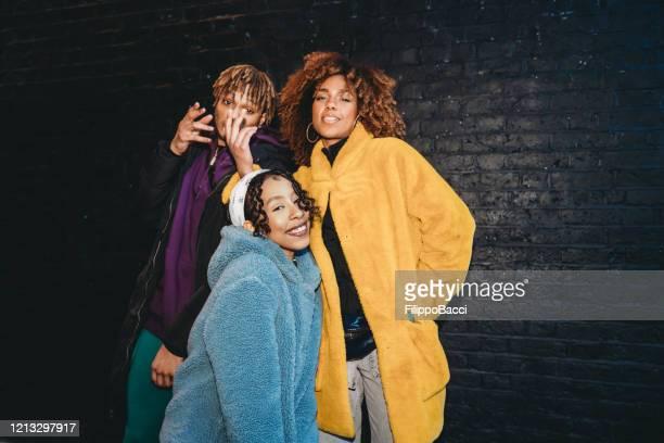 three friends dancing in the city against a black brick wall - hip hop music stock pictures, royalty-free photos & images