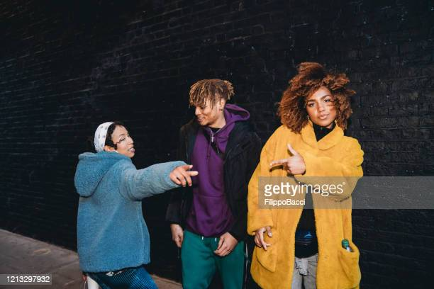 three friends dancing in the city against a black brick wall - street stock pictures, royalty-free photos & images