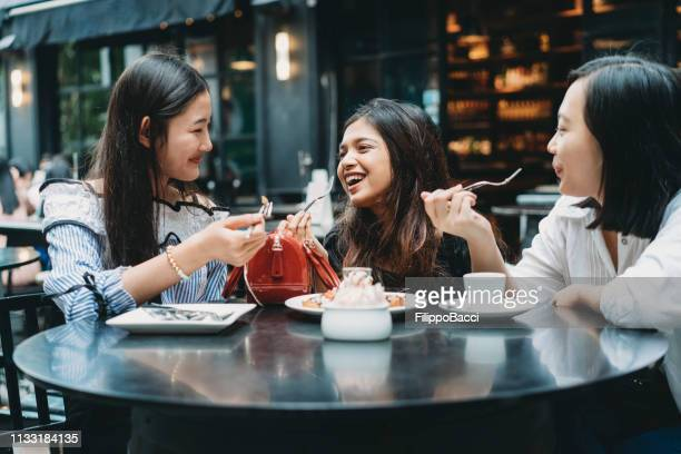 three friends eating a dessert at the restaurant together - thai ethnicity stock pictures, royalty-free photos & images